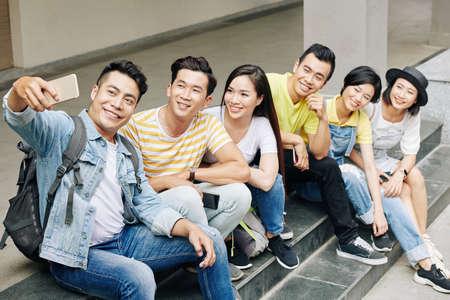 Foto de Cheerful Vietnamese university student taking selfie with friends sitting on steps - Imagen libre de derechos