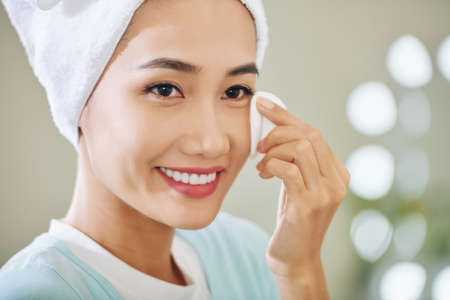 Photo pour Smiling attractive young Vietnamese woman wiping off her make-up - image libre de droit
