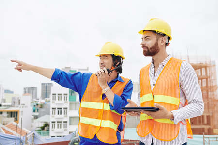 Photo for Smiling Vietnamese contractor talking on walkie-talkie and pointing away when standing next to head engineer with digital tablet in hands - Royalty Free Image