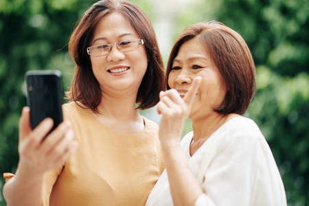 Photo for Asian senior women video calling their friend when standing outdoors - Royalty Free Image