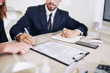 Photo pour Business lady showing business partner where to sign contract after discussing details of collaboration - image libre de droit