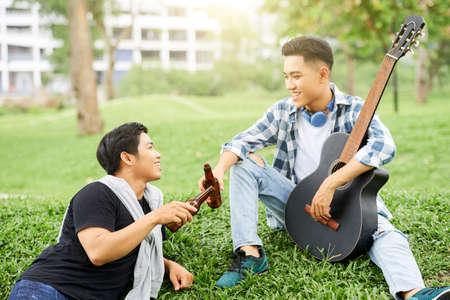 Foto de Two young men sitting on green grass with guitar and drinking beer outdoors - Imagen libre de derechos