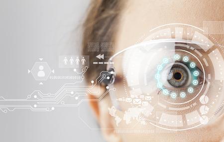 Foto de Young woman loking at virtual graphics in futuristic background - Imagen libre de derechos
