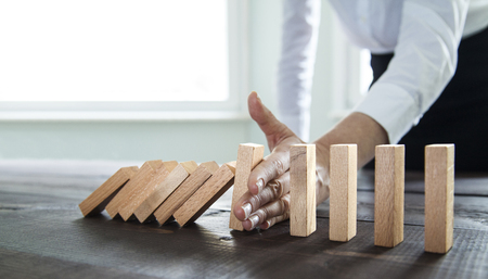 Photo pour Businesswoman stopping falling wooden dominoes effect - image libre de droit