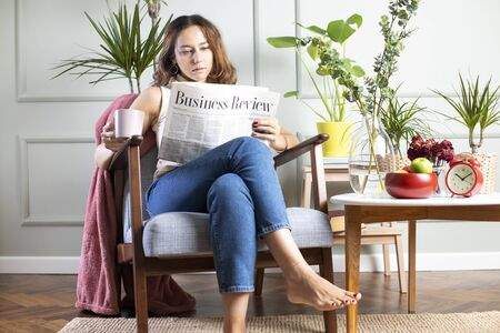 Young woman sitting by a living room and reading a newspapers. There are some houseplants on the table in front of her. Morning routine with newspapers
