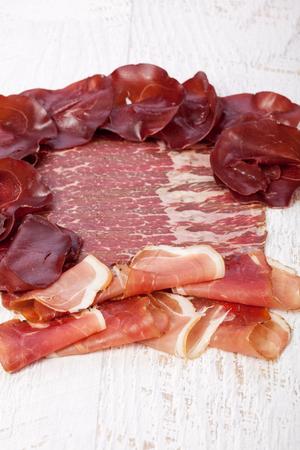 Delicious italian ham on wooden background. Restaurant appetizer