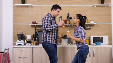 Young couple playing with kitchen tools while dinner gets ready. Funny moment.