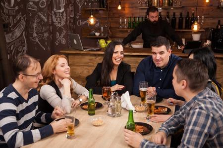 Foto de Group of young friends sitting around table in bar togethe. Cheerful mood. - Imagen libre de derechos