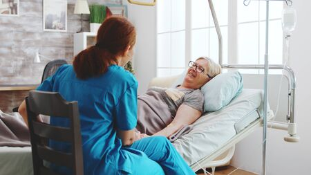 Photo pour In bright retirement home old lady lying in hospital bed talks with a female caregiver. - image libre de droit