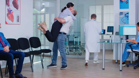 Husband hugging wife after receiving good news from doctor in hospital waiting area. Medic wearing white coat and stethoscope.