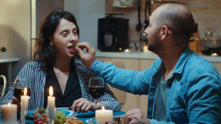 Happy funny couple in love eating grapes at dinner, smiling and having fun during romantic dinner. Wife and husband celebrating anniversary with red wine, tender moments at candle lights in kitchen