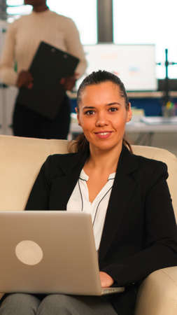 Photo pour Hispanic business woman smiling at camera sitting on couch typing on computer while diverse colleagues working in background. Multiethnic coworkers analysing startup financial reports in modern office - image libre de droit