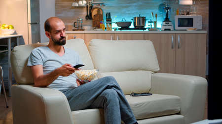 Photo for Bored man switching TV channels, holding popcorn in hads late at night while trying to watch entertainment television. Using remote control to choose favourite station and enjoy quality time - Royalty Free Image