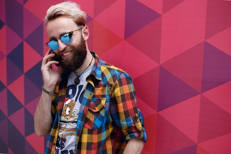 Photo pour Portrait of a handsome hippster young man talking on his mobil phone, isolated on a colorful hexagons geometric form background. - image libre de droit