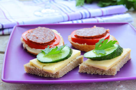 canape sandwiches with cheese and salami on the purple plate