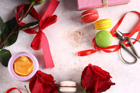 Photo pour holiday background with roses macaroons and gifts - image libre de droit