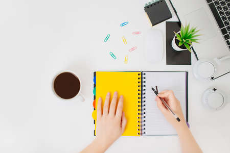 Foto de Woman workplace, female hands writing in a notepad. Flatlay with hands, coffee mug, headphones and notepad. - Imagen libre de derechos
