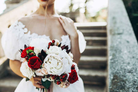 Photo pour Wedding bouquet with red and white flowers in brides hand. Close up, no face seen. - image libre de droit