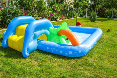 Photo pour A summertime garden with inflatable swimming pool in the background - image libre de droit