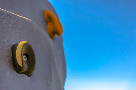 Close up of the foot and hand holds on a climbing wall against bright blue sky