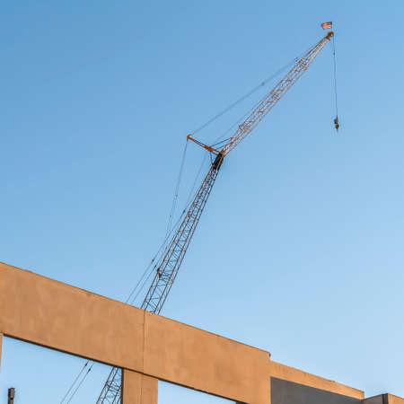 Foto de Square Building under construction with metal crane and blue sky background - Imagen libre de derechos