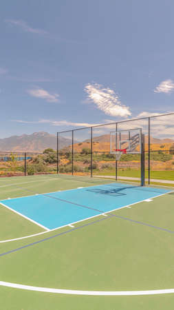 Vertical Outdoor green basketball court three point line. An outdoor, green basketball court and three point line on a clear, sunny day.