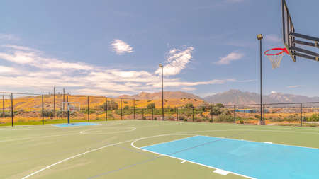 Panorama frame Outdoor basketball court and nets on sunny day. An outdoor green and blue turf basketball court and nets on a sunny, clear day.