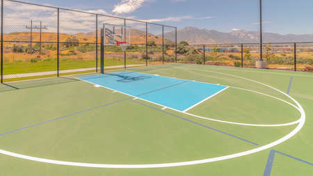 Panorama frame Outdoor green basketball court three point line. An outdoor, green basketball court and three point line on a clear, sunny day.