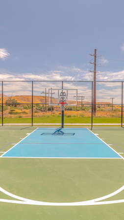Vertical Outdoor basketball court and three point line. An outdoor basketball court and three point line on a clear, sunny day.