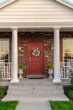Photo for Front door to a house flanked by two pillars. Front door to a face brick house flanked by two pillars and windows with a dried wreath hanging on the wood - Royalty Free Image