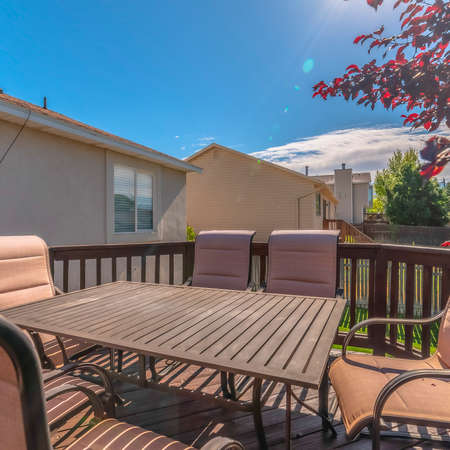 Photo for Square Table and chairs on the balcony of a home with stairs going down to the yard. The outdoor living space has a peaceful view of trees and blue sky on a sunny day. - Royalty Free Image