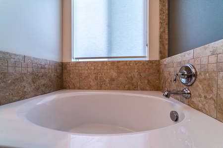 Photo pour Small bathtub with mixer tap on a beige tiled wall below a frosted window - image libre de droit