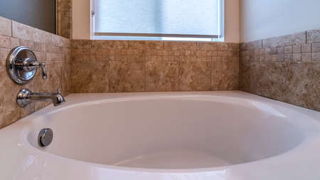 Photo pour Panorama frame Small bathtub with mixer tap on a beige tiled wall below a frosted window - image libre de droit