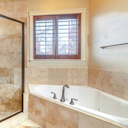 Photo pour Square frame Modern luxury bathroom with glass shower cubicle, fitted corner bath and beige travertine tiles - image libre de droit