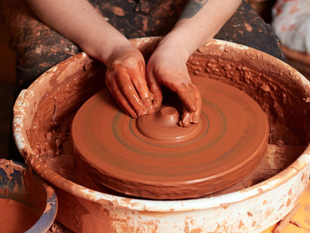 Photo pour production process of pottery. Forming the clay cover of the kettle on the potter's wheel. - image libre de droit
