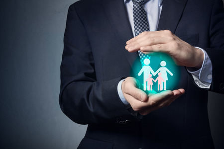Photo pour Family insurance. A businessman is holding a family pictogram on his hand. Protection of the family and marriage. - image libre de droit