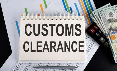 Photo pour Customs Clearance text written on notebook with chart, calculator and dollars - image libre de droit