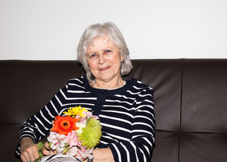 A woman showing that she enjoys retirement by relaxing and holding flowers.