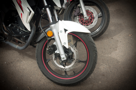 Photo closeup of a motorcycle front wheel with a red stripe.