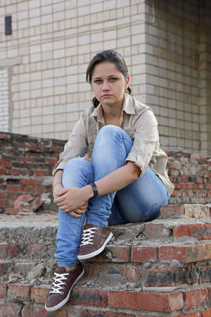 Resentful young woman sitting on the destroyed wall of the building
