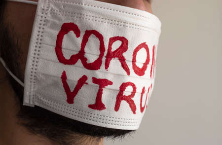 Closed up to a CORONAVIRUS man patient with beard using a white face mask with red CORONAVIRUS inscription. Concept photography COVID-2019