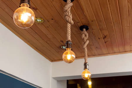 Photo for three artesanal yellow light bulbes with wooden roof and blue & white paiting. Interior design concept - Royalty Free Image