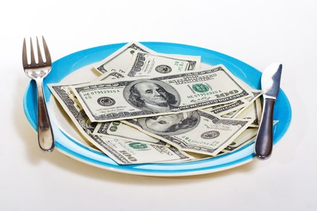 Money on plate with fork, knife and spoon. Economy and business concept