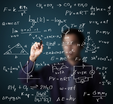 male teacher writing various high school maths and science formula on whiteboard