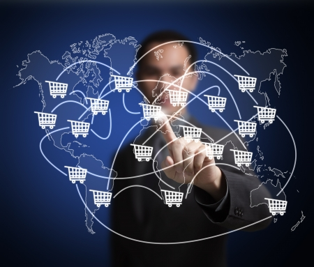 business man pointing at worldwide cart network on world map -  symbol of modern online trade and marketing