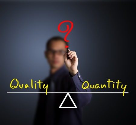 business man writing quality and quantity compare on balance bar