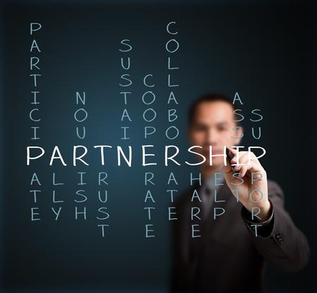 Foto de business man writing partnership concept by crossword of relate word such as ally, sustain, help, support, assist, share, etc  - Imagen libre de derechos