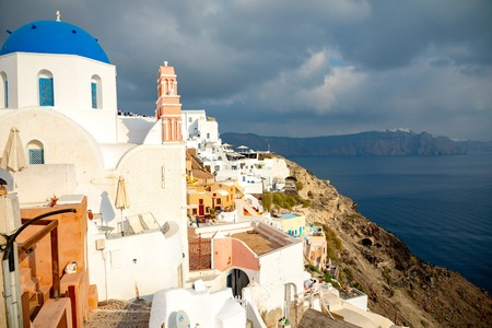 Traditional and famous houses and churches with blue domes in Oia, Santorini in Greece