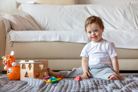 Foto de Cute small boy with Down syndrome playing with toy in home living room - Imagen libre de derechos