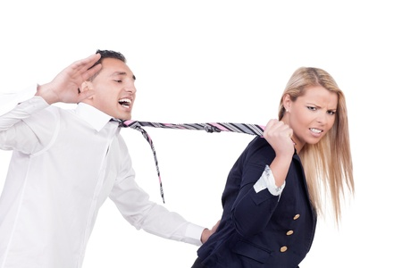 Attractive blonde woman with a disgruntled frowning expression pulling a protesting man along behind her by his tie isolated on white